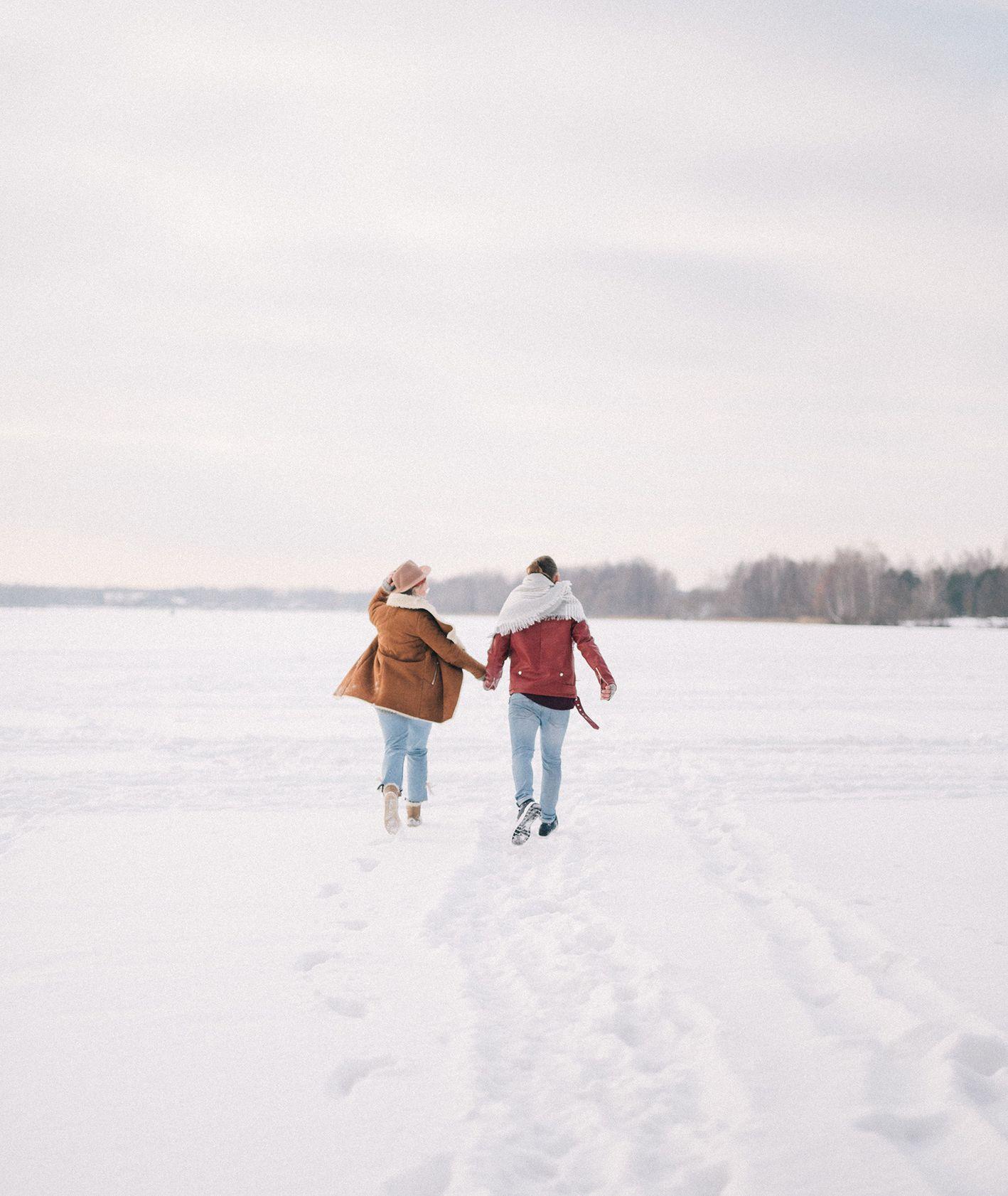 Dwoje ludzi trzymających się za ręce i spacerujących po śniegu (fot. Olya Kobruseva / pexels.com)