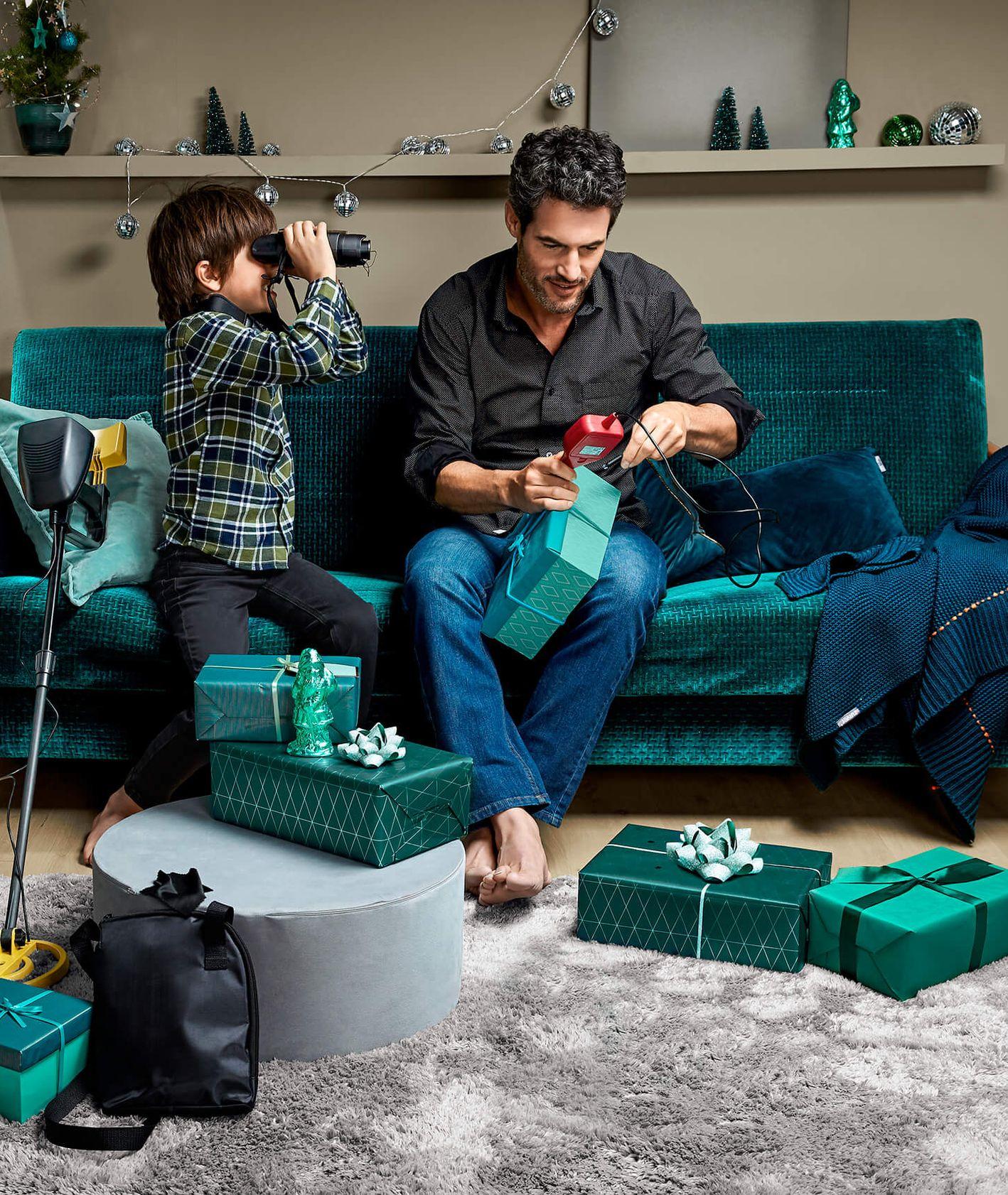 Tata wraz synem odpakowujący świąteczne prezenty, mała choinka w doniczce, świetlna girlanda i świąteczne pakunki na podłodze