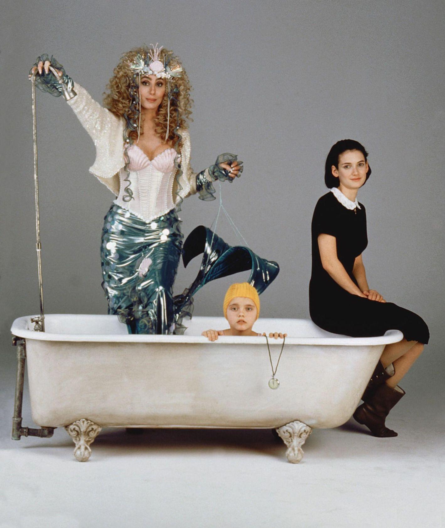 """Kadr z filmu """"Syreny"""" – mama Rachel Flax w stroju syreny, wchodzi do wanny, w której siedzi jej młodsza córka w kąpielowym czepku, obok starsza córka w czarnej sukience, siedząca na brzegu wanny"""