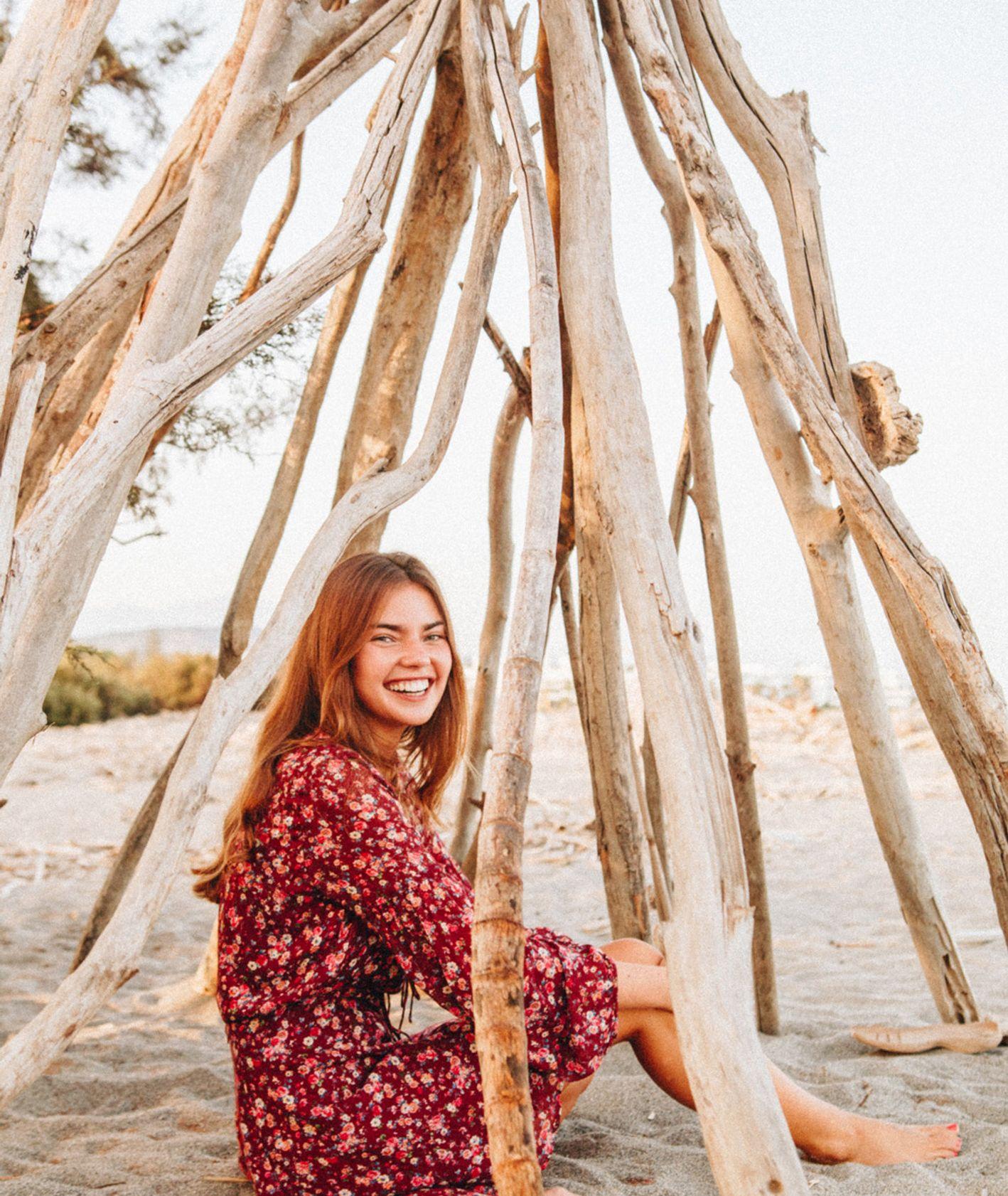 Uśmiechnięta kobieta siedząca pod konstrukcją z gałęzi na plaży. (fot. Sonnie Hiles / unsplash.com)